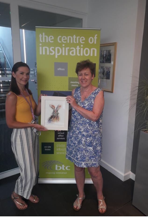 Sophie Hearle (left) receiving her chosen artwork 'Pucker Up Mr Hare' from Jennifer Foulds at the btc stevenage